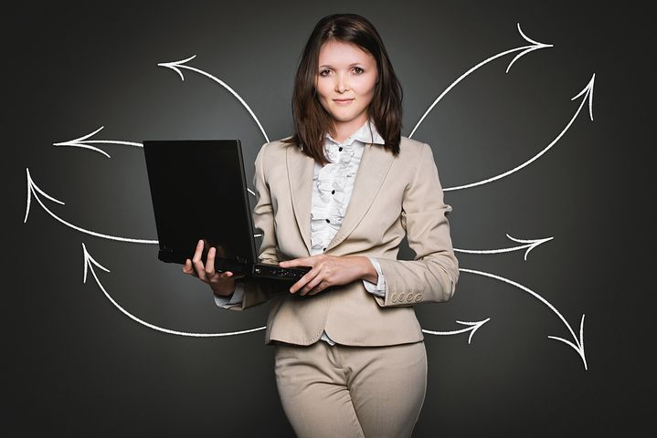 Analytics: woman in business suit holding a laptop with arrows