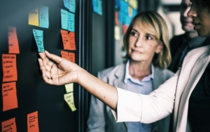 two women review sticky notes on board